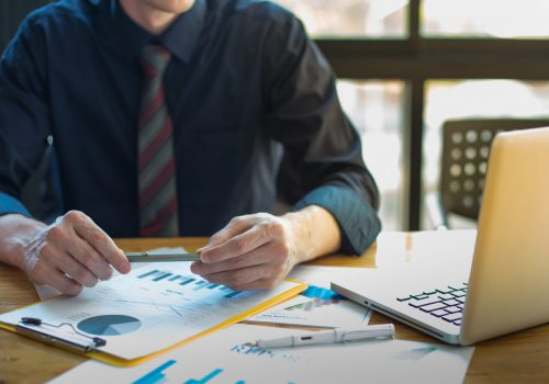 business documents on office table and graph business with social network diagram and man working in the background.